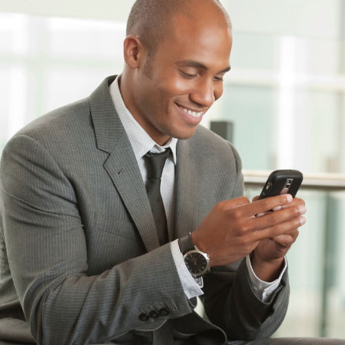 business man texting, smiling at his phone