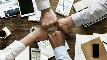 financial services teamwork, four people fist bumping over a desk