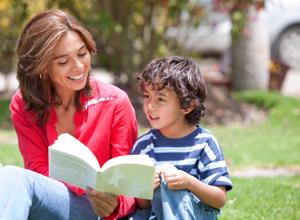 Beautiful portrait of a mothe and her son reading at the park